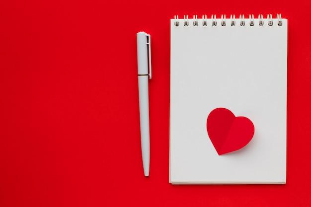 Liebesherz auf notizblock mit stift auf hellrotem hintergrund. valentinstag thema. flache lage, draufsicht, kopierraum.