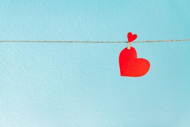 Liebesherz, das am seil auf einem blauen hintergrund hängt