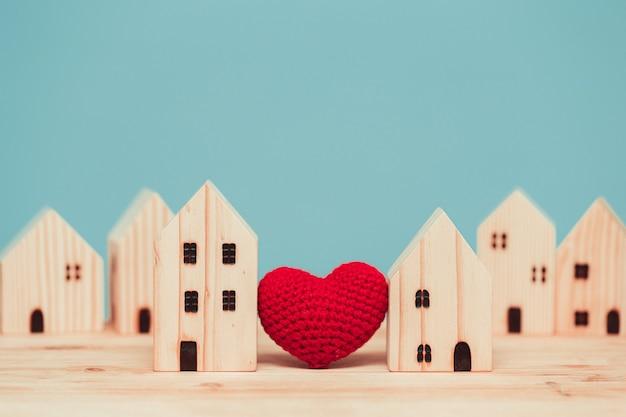 Liebesherz zwischen zwei holzmodellen für den aufenthalt zu hause für ein gesundes gemeinschaftskonzept.