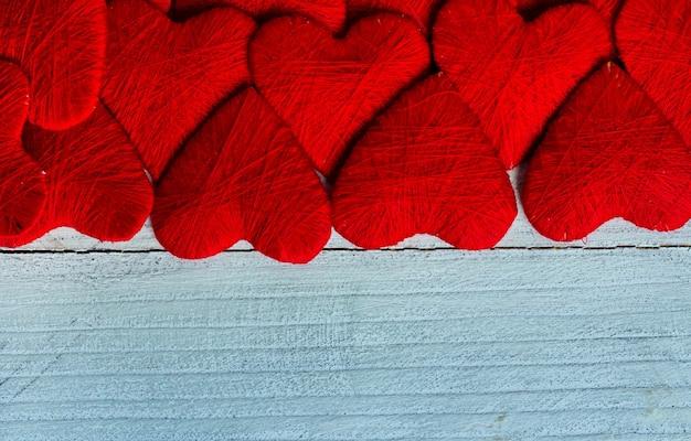 Liebesherzen auf hölzernem texturhintergrund valentinstagskartenkonzept