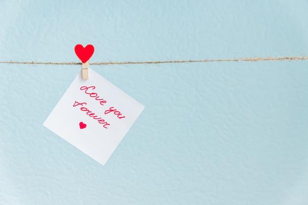 Liebesherzstift des roten valentinsgrußes, der an der natürlichen schnur gegen blauen hintergrund hängt. gezeichnetes herz auf papierstück.