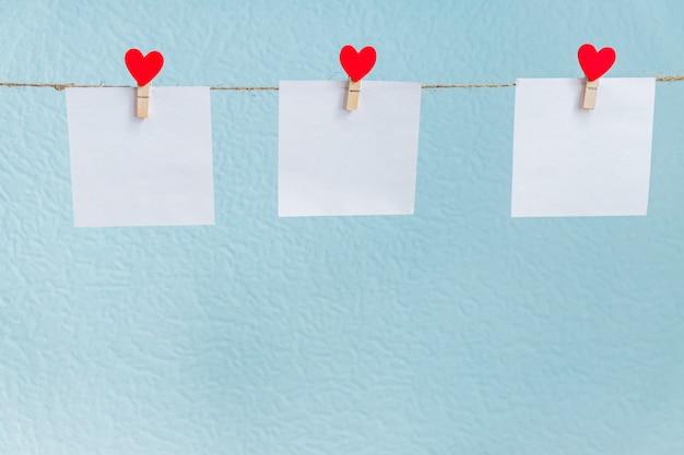 Liebesherzstifte des roten valentinsgrußes, die an der natürlichen schnur gegen blauen hintergrund hängen. mock-up-konzept für ihren text