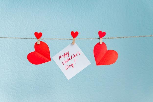 Liebesherzstifte des roten valentinsgrußes, die an der natürlichen schnur gegen blauen hintergrund hängen.