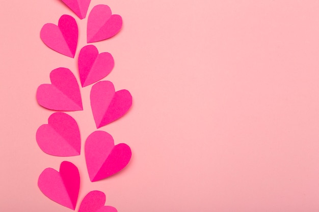 Liebeshintergrund (valentinstag) oder hochzeitshintergrund. rosa papierherzen auf einem rosa pastellhintergrund. liebeskonzept
