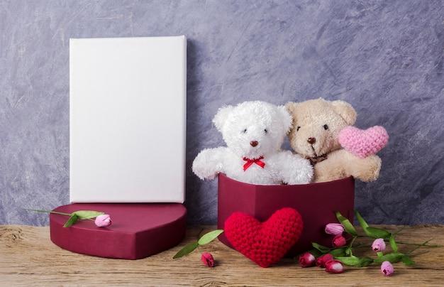 Liebeskonzept des teddybären in der roten herzgeschenkbox auf hölzerner tabelle und leerem segeltuchrahmen