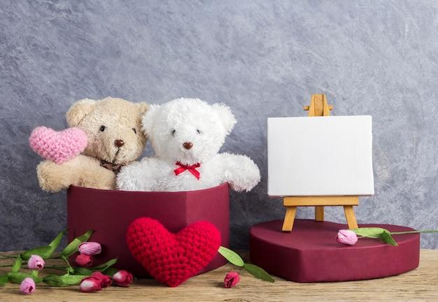 Liebeskonzept des teddybären in der roten herzgeschenkbox und im leeren segeltuchrahmen auf gestellmalerei