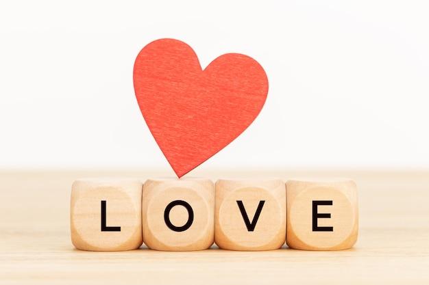 Liebeskonzept. holzblöcke mit text und hölzernem herzen auf tisch.