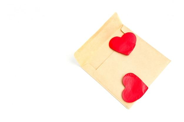 Liebeskonzept: liebe auf abstand, liebesbrief, valentinstag handwerksumschlag mit rotem herzen auf weiß