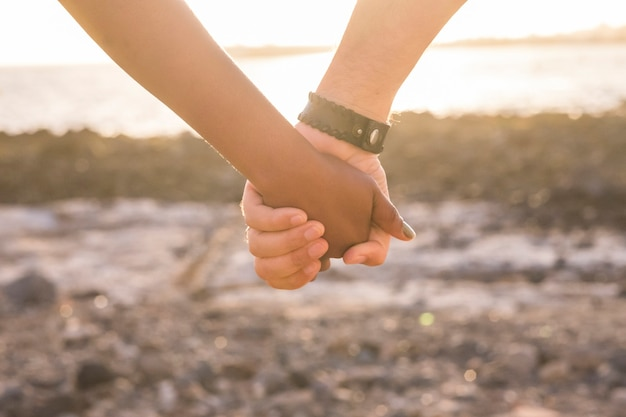Liebeskonzept mit schwarzer und weißer hand, die während eines goldenen sonnenuntergangs den ozean berührt und nimmt