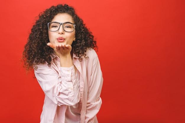 Liebeskonzept. porträt eines jungen schönen brünetten mädchens, das einen kuss bläst, lokalisiert auf rotem hintergrund.