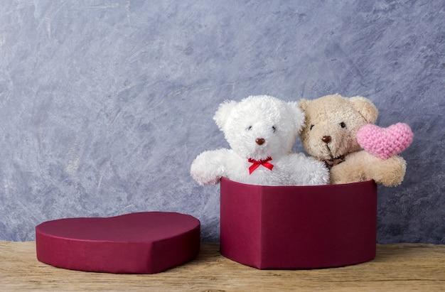 Liebeskonzepte des teddybären in der roten herzgeschenkbox, die rosa herz auf hölzerner tabelle hält