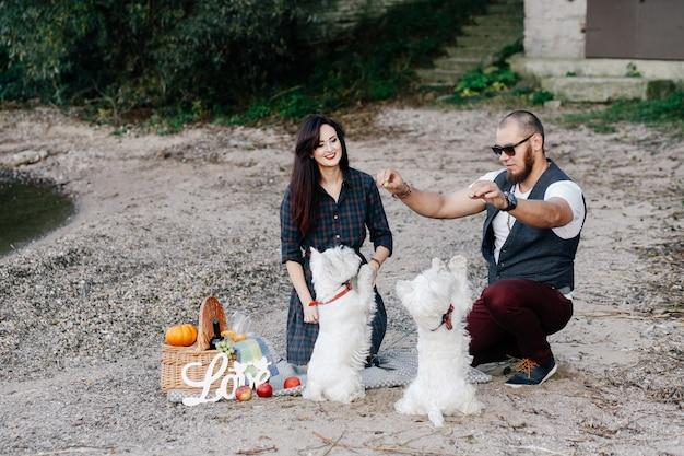 Liebespaar am strand spielen mit ihren weißen hunden