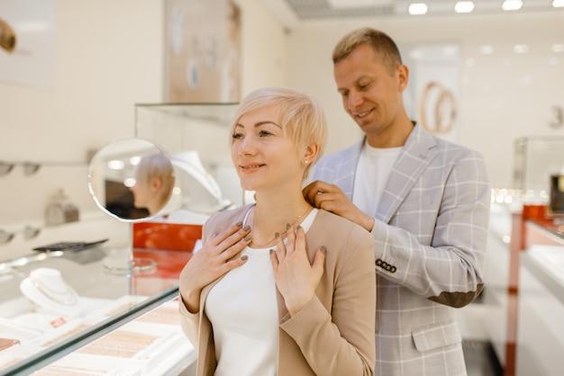 Liebespaar, das an goldkette versucht. männliche und weibliche kunden, die auf juwelen im juweliergeschäft schauen. mann und frau kaufen goldene dekoration. zukünftige braut und bräutigam im juweliergeschäft