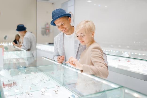 Liebespaar, das auf juwelen im juweliergeschäft schaut
