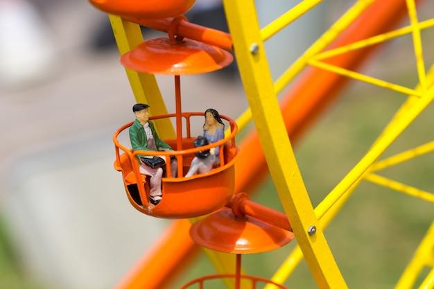 Liebespaar, das ein riesenrad reitet, miniaturszene im freien, europa. mini figuren mit hoher entkalkung von objekten, realistisches diorama, spielzeugmodell