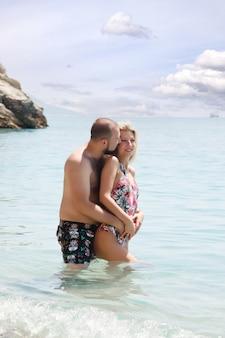 Liebespaar, das flitterwochen am strand in der lagune mit luxuriösem blick auf meereshintergrund genießt. glückliche liebhaber auf romantischer reise haben spaß im sommerurlaub. konzept romantik und entspannung. platz kopieren