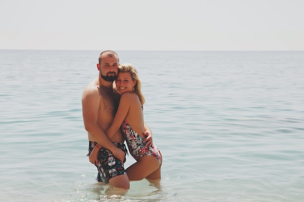 Liebespaar, das flitterwochen am strand in der lagune mit luxuriösem blick auf meereshintergrund genießt