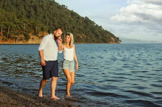 Liebespaar, das flitterwochen auf dem territorium strandhotel mit luxuriösem blick zu fuß genießt, zeigt emotionen auf dem meereshintergrund. glückliche liebhaber auf romantischem reisespaß im sommerurlaub. konzept romantik und entspannung