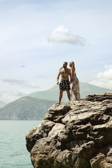 Liebespaar, das flitterwochen auf felsen mit luxuriösem blick genießt und emotionen auf azurblauem meereshintergrund zeigt. glückliche liebhaber auf romantischer reise haben spaß im sommerurlaub. konzept romantik und entspannung
