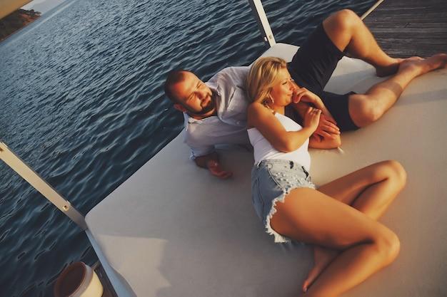 Liebespaar, das flitterwochen im strandhotel mit luxusblick genießt, zeigt emotionen auf dem meereshintergrund