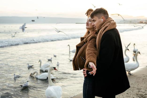 Liebespaar, das im winter musik über kopfhörer am strand hört