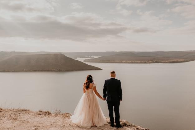 Liebespaar, das jungvermählten im weißen kleid und im anzug heiratet, gehen im sommer auf berg über fluss. sonnenuntergang und sonnenaufgang