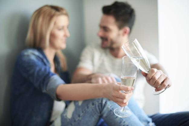 Liebespaar, das mit champagner auf neues zuhause anstößt