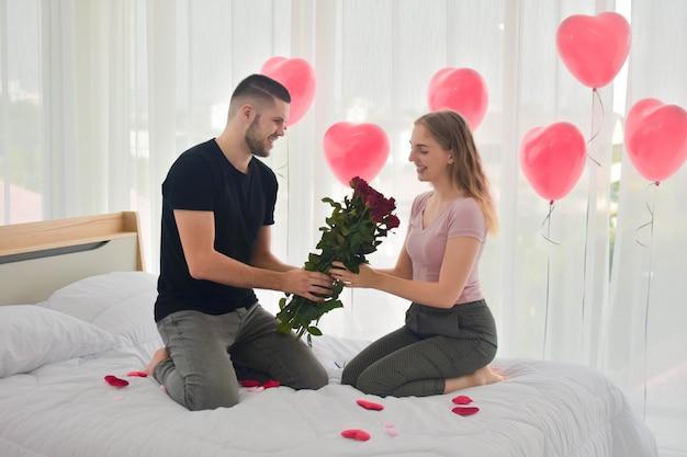 Liebespaar, das rosenblume im schlafzimmerglück im liebes-valentinstagkonzept gibt