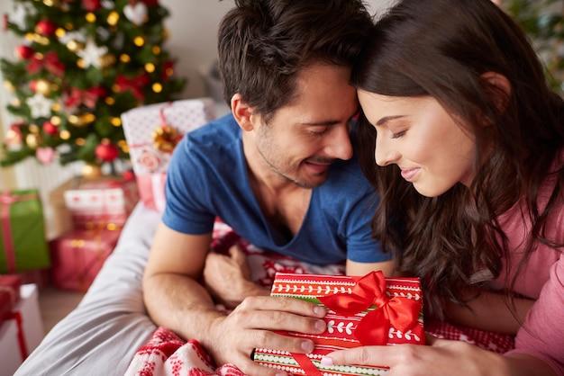 Liebespaar, das während der weihnachten im bett liegt