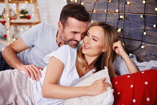 Liebespaar, das weihnachten im bett feiert