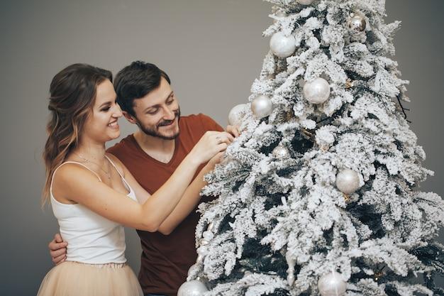 Liebespaar, das weihnachtsbaum verziert. glückliche familie