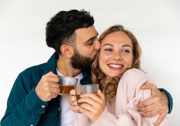 Liebespaar, das zu hause zusammen tee macht