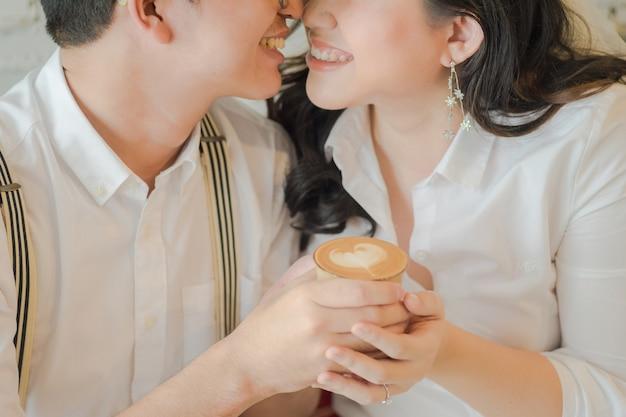 Liebespaar halten eine schale lattekunst mit herzmuster in einer weißen schale an