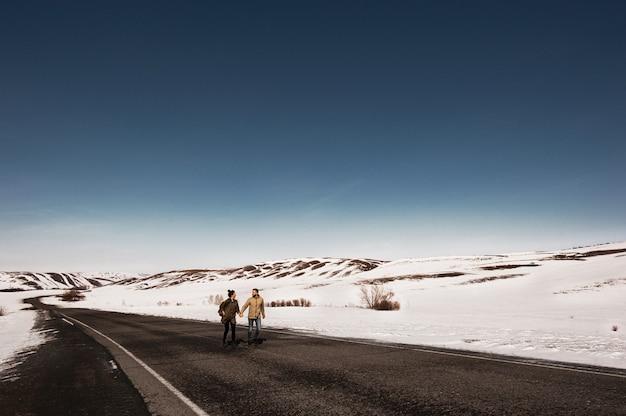 Liebespaar im winter läuft auf der straße zwischen den bergen. mann und frau rennen die straße runter. winterreise. ein verliebtes paar reist.