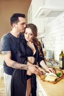 Liebespaar in der küche umarmt morgens und bereitet frühstück zu. glückliche familie