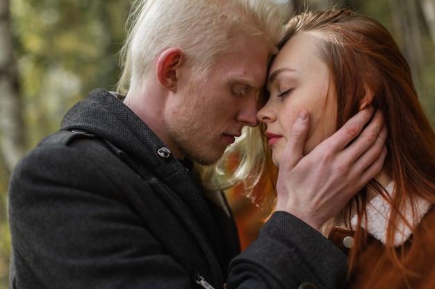 Liebespaar in einem grünen park an einem sonnigen klaren tag. ein mann mit blonden haaren und ein mädchen mit roten haaren umarmen sich.