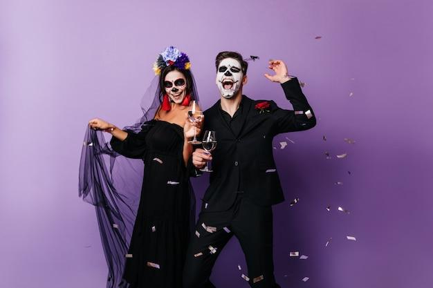 Liebespaar in gruseliger kleidung, das den tag der toten feiert. freudiges mädchen und junge tanzen auf halloween-party.