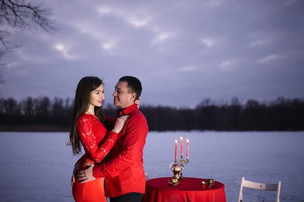 Liebespaar in schönen roten kleidern auf der straße stehen nahe dem tisch mit winterschneehintergrund