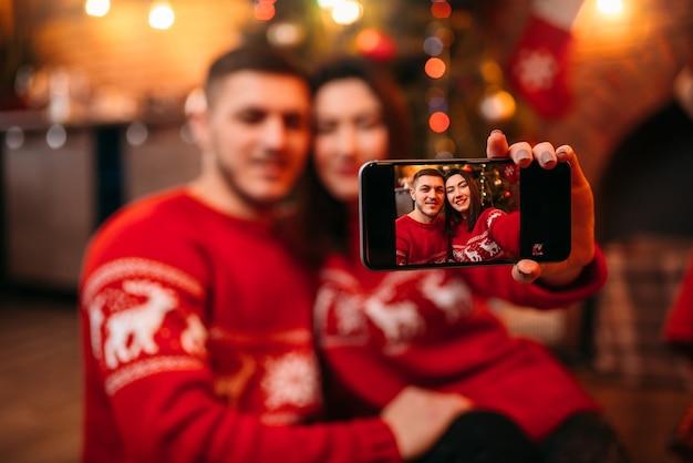 Liebespaar macht selfie auf telefonkamera, romantische weihnachtsfeier. weihnachtsferien, mann und frau glücklich zusammen, festliche dekoration