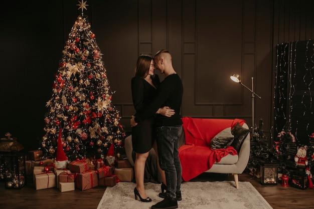 Liebespaar mann und frau, die küssen nahe weihnachtsbaum umarmen