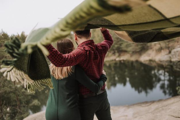 Liebespaar mit einem teppich, der sich im wind am ufer eines sees mit einer steilen klippe entwickelt