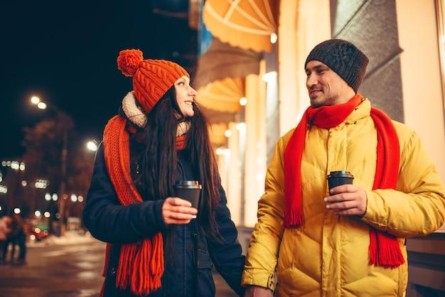 Liebespaar mit kaffee, der die straße entlang geht