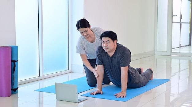 Liebespaar online lernen yoga-atmung und meditation zusammen zu hause. sport und bewegung für gesunde. asiatische frau und mann lebensstil.