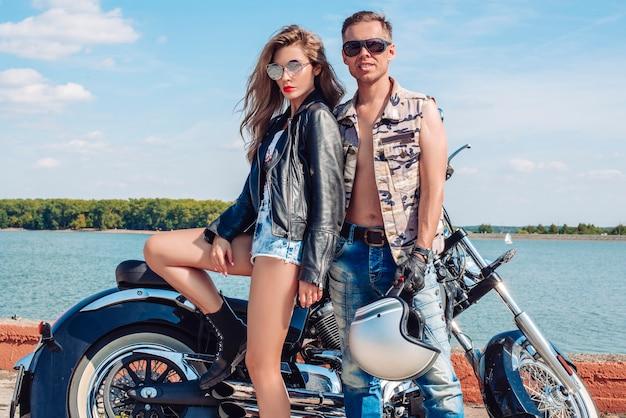 Liebespaar reist auf einem motorrad in der nähe des ozeans. familie, tourismus, liebeskonzept. gemischte medien