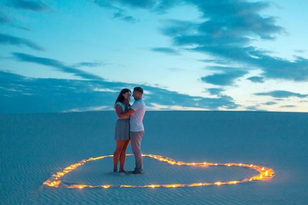 Liebespaar romantische umarmungen in der sandwüste. abend, romantische atmosphäre, in sand brennen kerzen in form von herzen