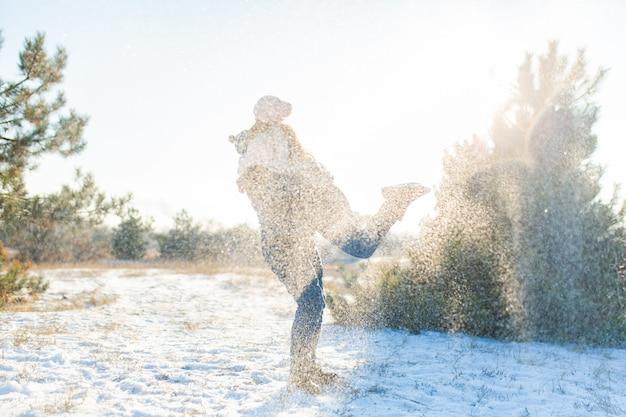 Liebespaar schneebälle spielen im winter im wald. wirf einander schnee. lachen und eine gute zeit haben