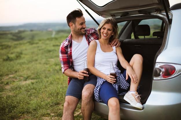 Liebespaar sitzt im auto trank während der reise in der natur