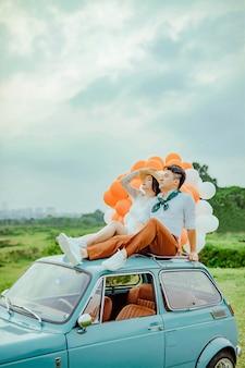 Liebespaar sitzt oben auf dem auto mit bunten luftballons