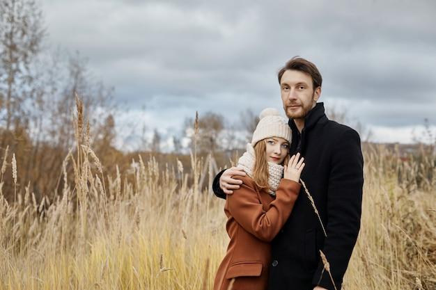 Liebespaar spaziergänge im herbst park, umarmungen und küsse. frau in den armen eines mannes im wald im frühjahr. liebhaber lieben sich und umarmen
