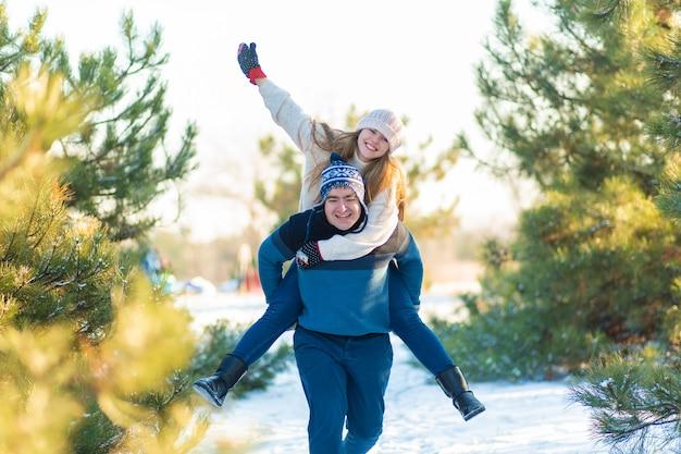 Liebespaar spielen im winter im wald. mädchen reitet einen mann im hintergrund des weihnachtsbaumes. lachen und eine gute zeit haben